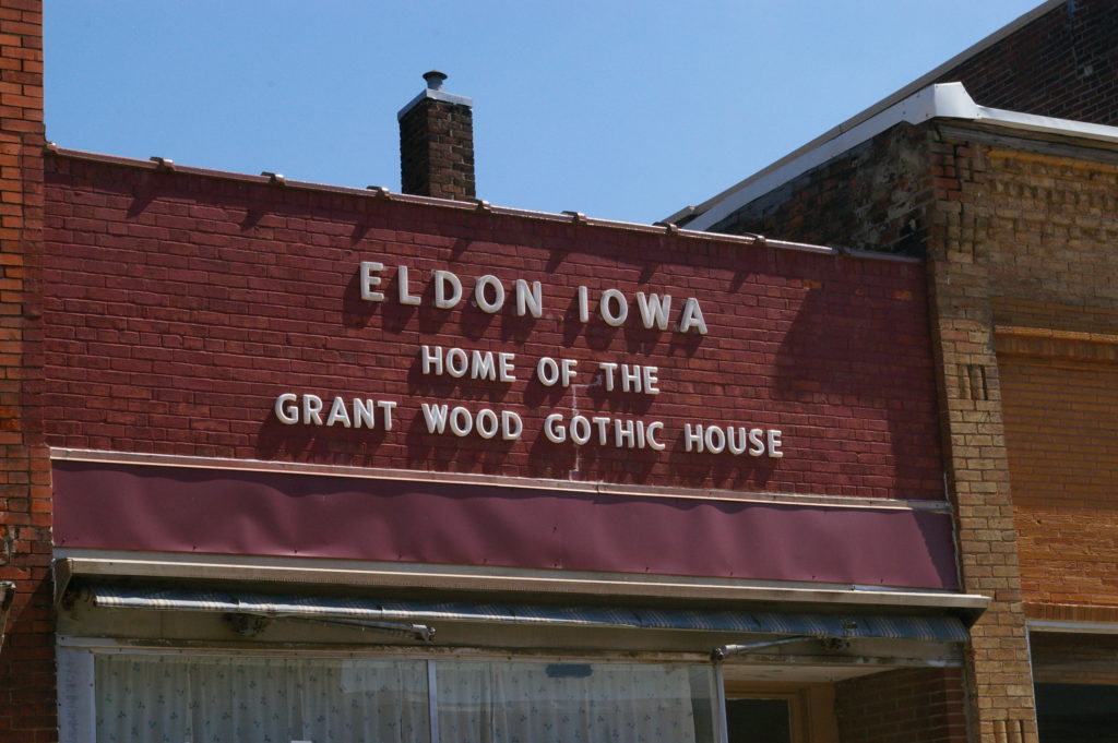 "White letters on the exterior of a red brick building reading ""Eldon, Iowa: Home of the Grant Wood Gothic House"" in Eldon, Iowa"