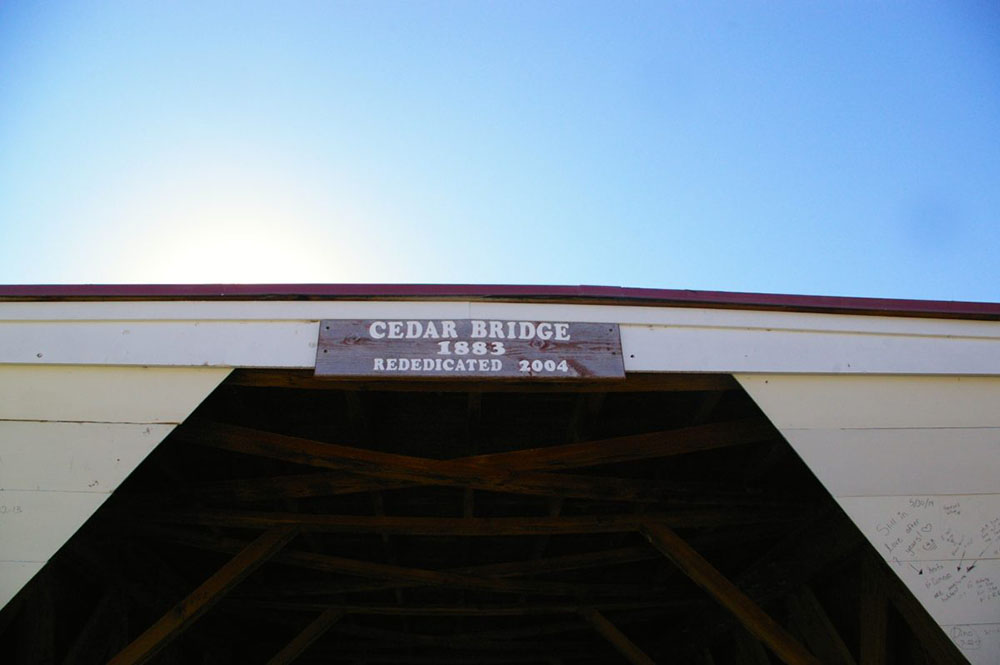 "Sign that reads ""Cedar Bridge 1883: Rededicated 2004"" at the white painted entrance of the Cedar Covered Bridge, , one of the six remaining Bridges of Madison County near Winterset, Iowa"