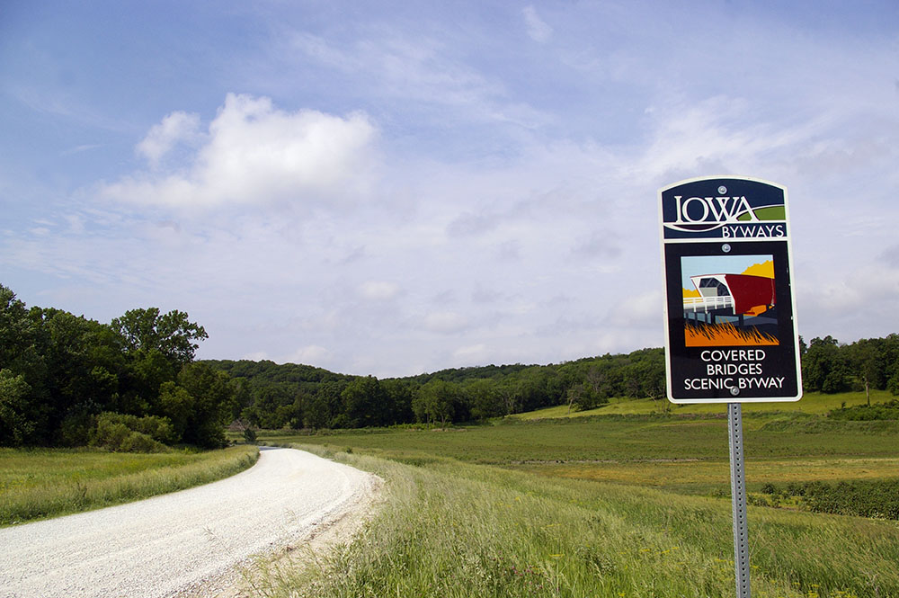 Sign for Covered Bridges Scenic Byway in a rolling green field near Winterset, Iowa