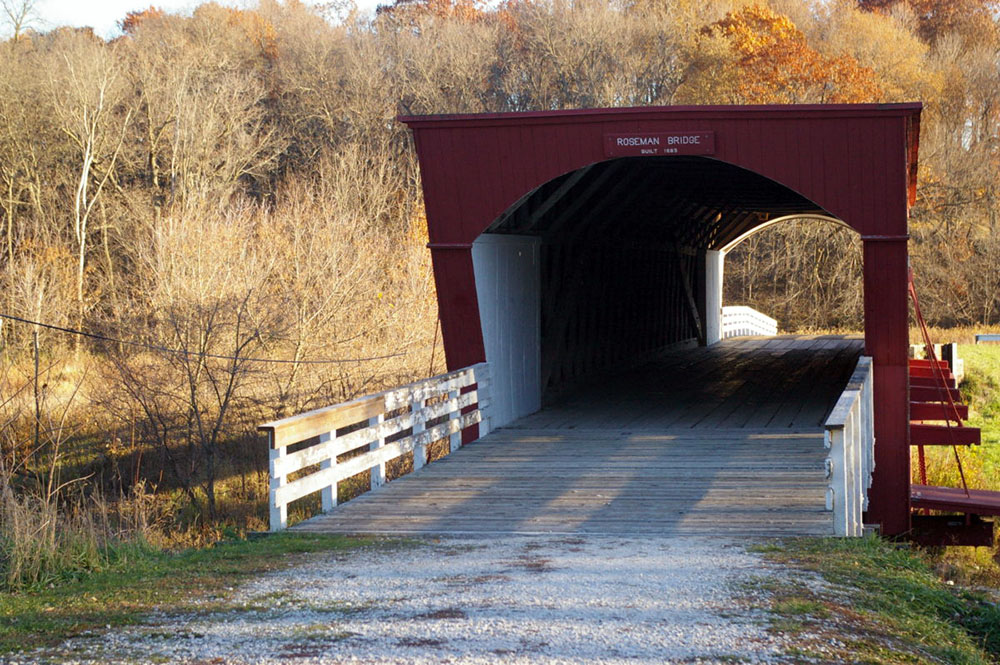 Wooded hills behind red and white painted exterior of Roseman Covered Bridge, one of the six remaining Bridges of Madison County near Winterset, Iowa