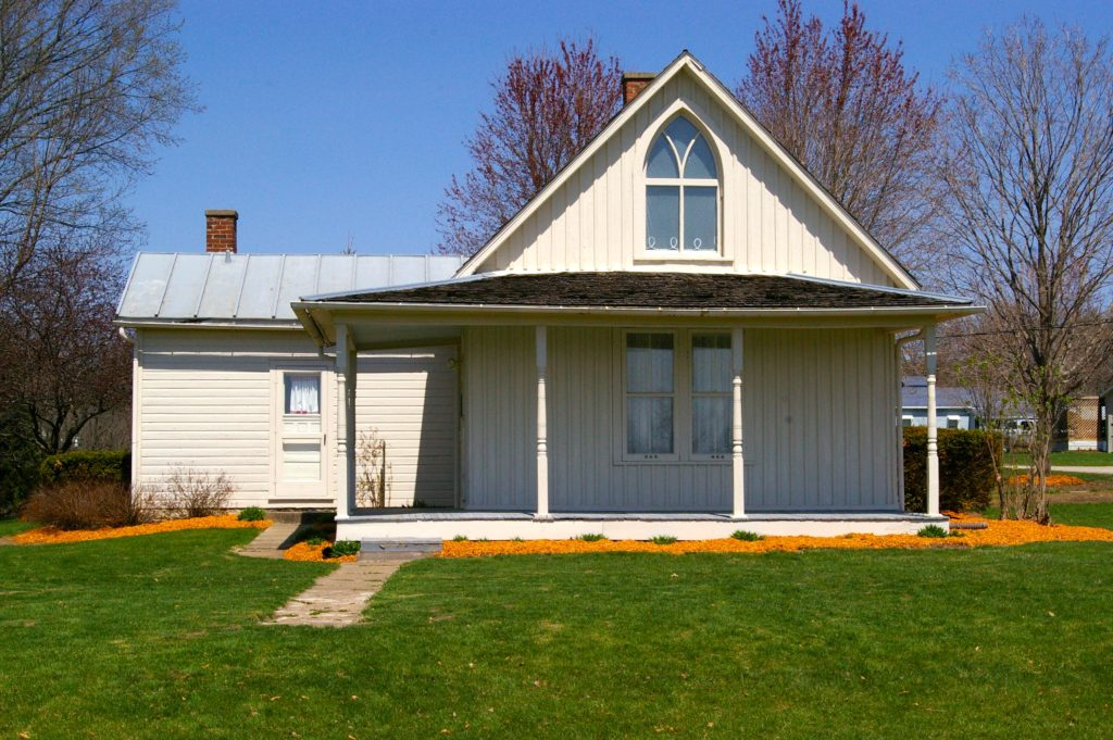White painted exterior and covered front porch of American Gothic House in Eldon, Iowa