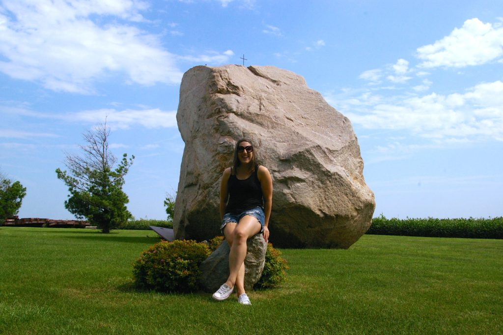 Woman sitting in front of giant boulder known as Slayton Rock near Casey, Iowa