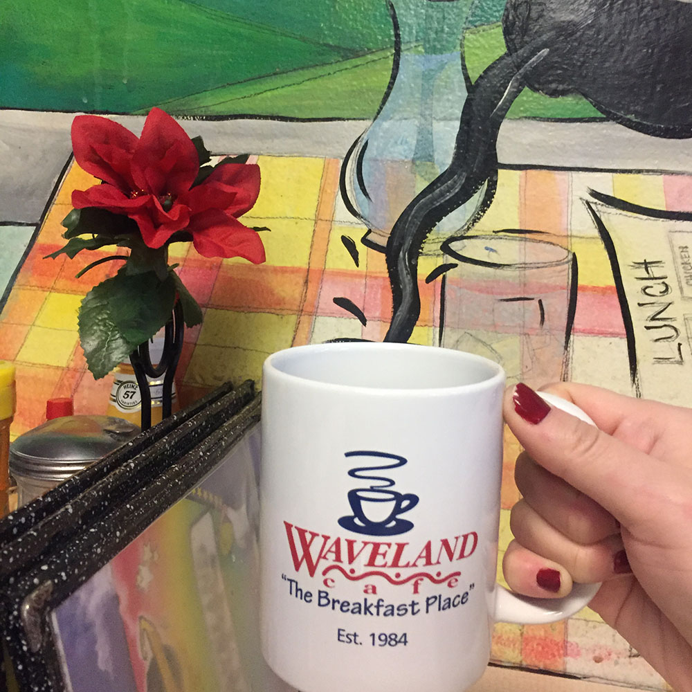"White coffee cup reading ""Waveland Cafe"" in front of coffee pouring mural at the Waveland Cafe in Des Moines, Iowa"