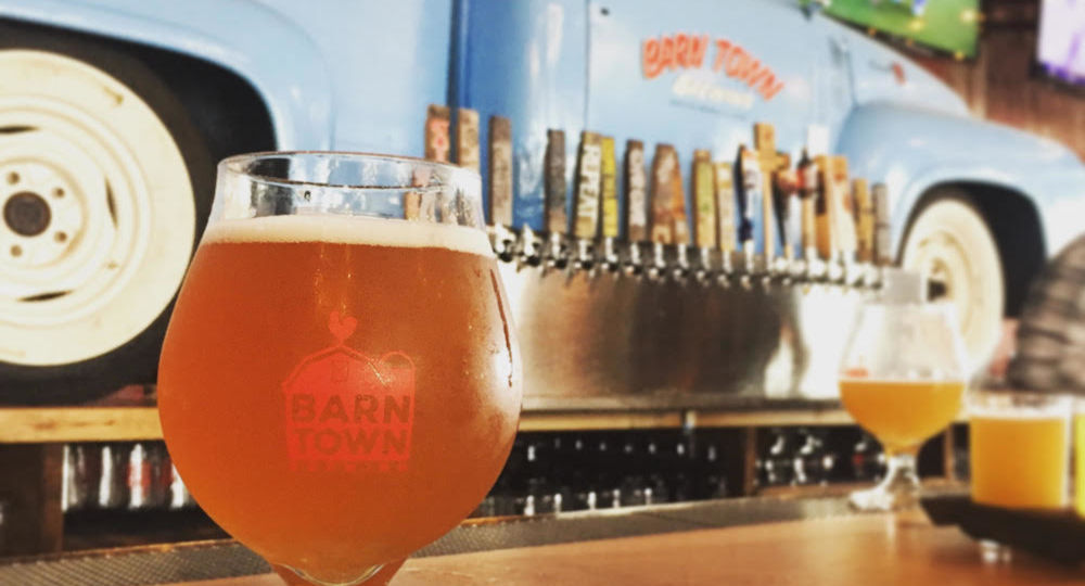 """Beer in a tulip glass reading """"Barn Town Brewing"""" on a wood bar in front of a wall with blue pickup truck backer and beer taps at Barn Town Brewing near Des Moines, Iowa"""