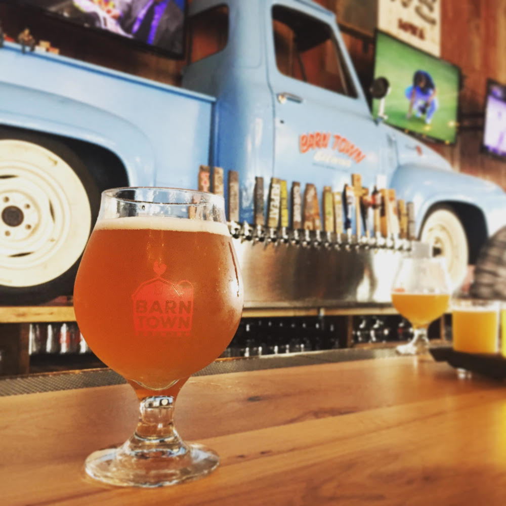 "Beer in a tulip glass reading ""Barn Town Brewing"" on a wood bar in front of a wall with blue pickup truck backer and beer taps at Barn Town Brewing near Des Moines, Iowa"