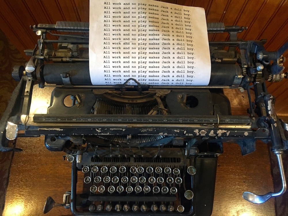 "Vintage typewriter with a piece of paper reading ""All work and no play makes Jake a dull boy"" over and over at the Stanley Hotel in Estes Park, Colorado"