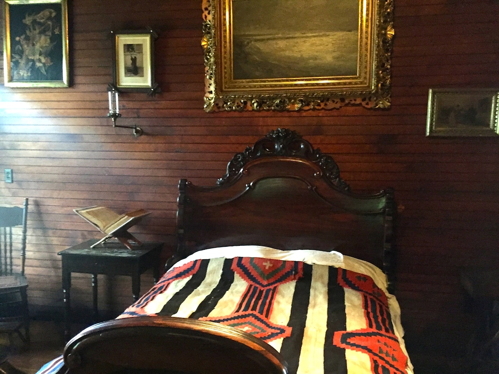 Carved bed frame in the bedroom of the historic Tinker Swiss Cottage in Rockford, Illinois