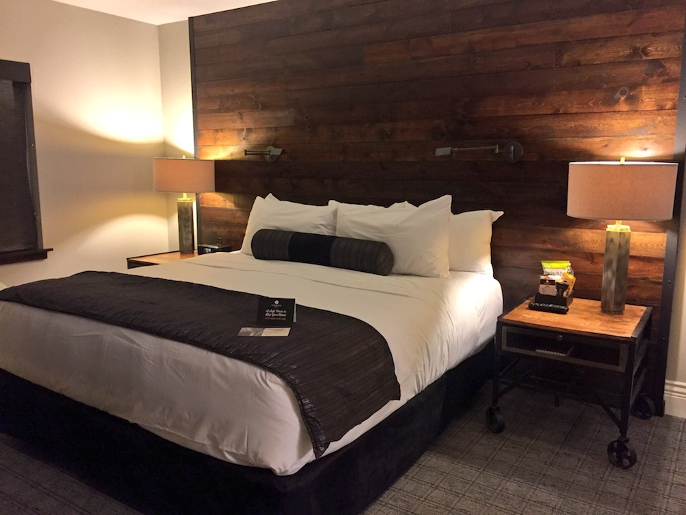 Bed with two end tables at Ironworks Hotel in Beloit, Wisconsin