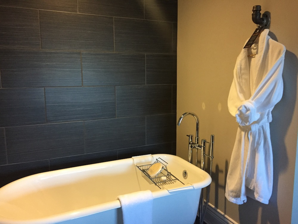 Deep soaker tub and bathrobe at Ironworks Hotel in Beloit, Wisconsin