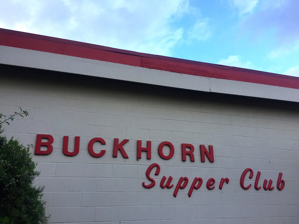 Red lettered sign on white brick at the Buckhorn Supper Club in Milton, Wisconsin