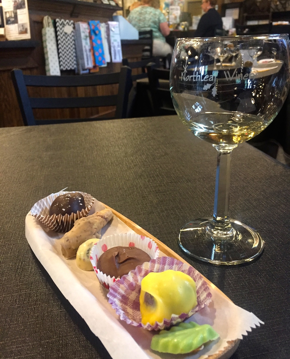 Glass of white wine paired with handmade chocolates at Northleaf Winery near Janesville, Wisconsin