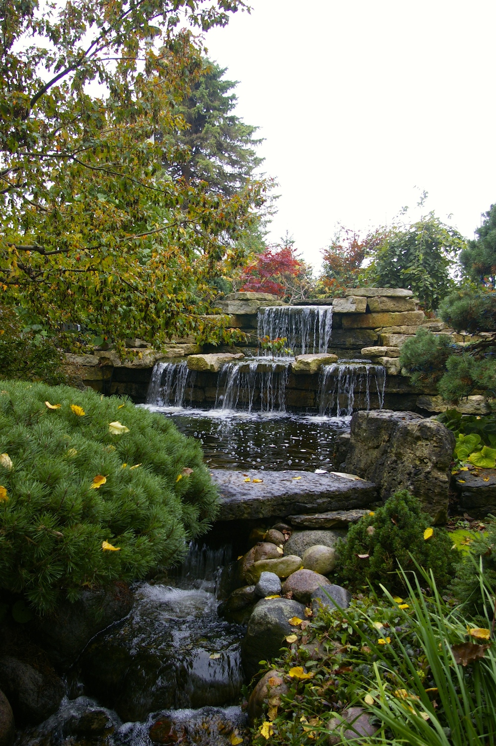 Waterfall against fall foliage at the Rotary Botanical Garden in Janesville, Wisconsin
