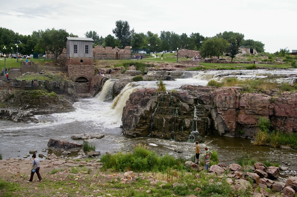 Visitors exploring the falls with historic buildings in the background at Falls Park in Sioux Falls, South Dakota