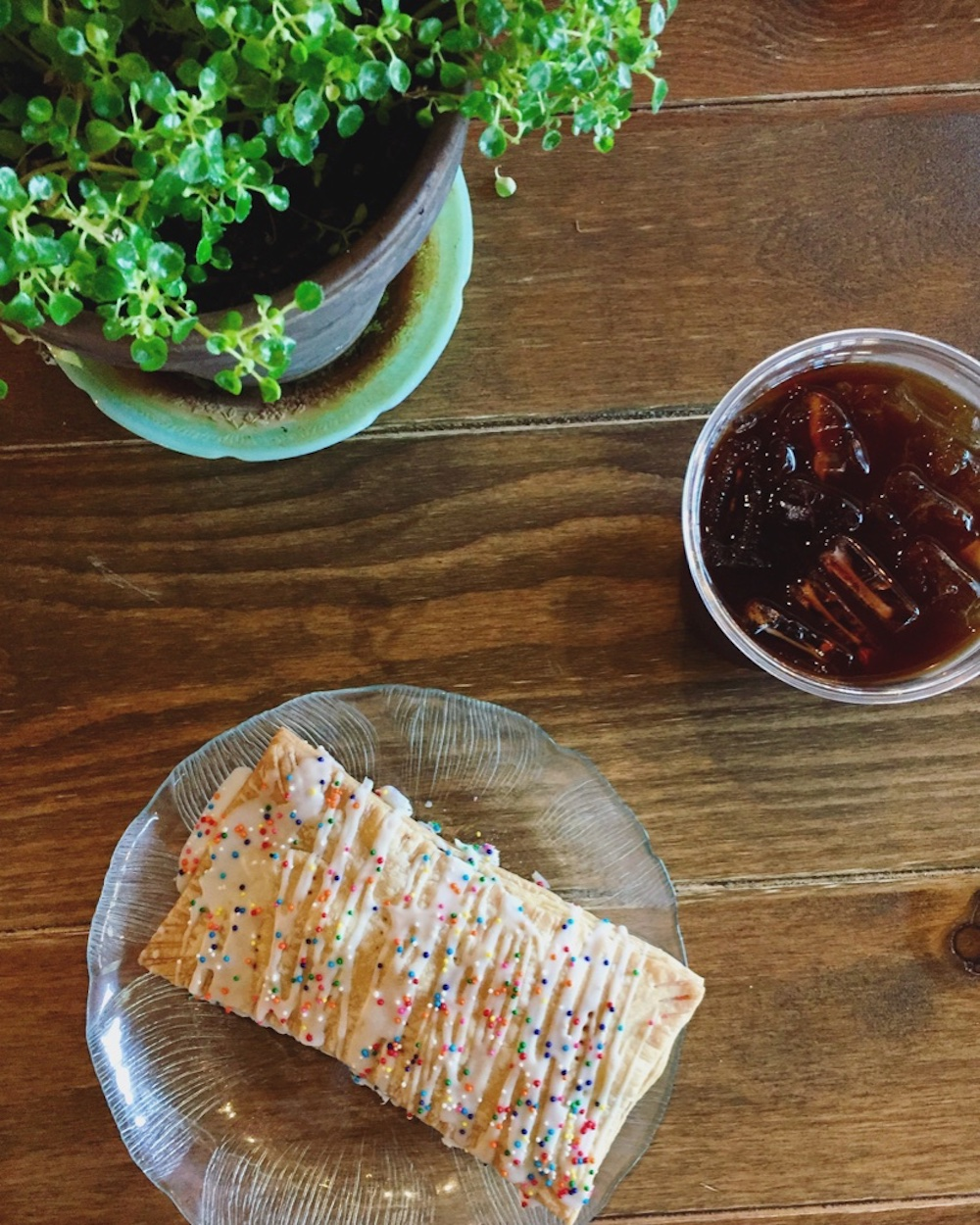 Aerial view of homemade poptart with rainbow sprinkles, plant, and iced coffee at Josiah's Coffeehouse in Sioux Falls, South Dakota