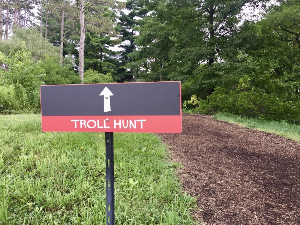 Black and red sign for the Morton Arboretum Troll Hunt in Lisle, Illinois