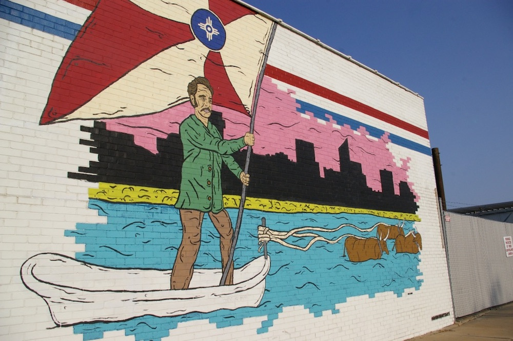 Mural of man crossing a river holding the Wichita flag in the Douglas Design District of Wichita, Kansas