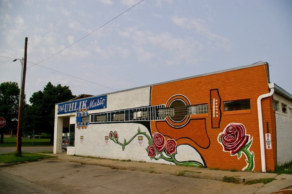 Giant orange guitar with roses painted on the side of a building in the Douglas Design District of Wichita, Kansas.