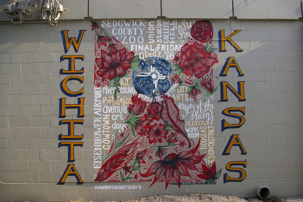 Mural of a modified Wichita flag made up of words and roses in the Douglas Design District of Wichita, Kansas