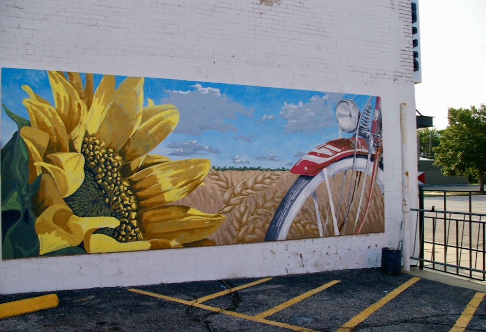 Sunflower mural with bike and field of sunflowers in the Douglas Design District in Wichita, Kansas