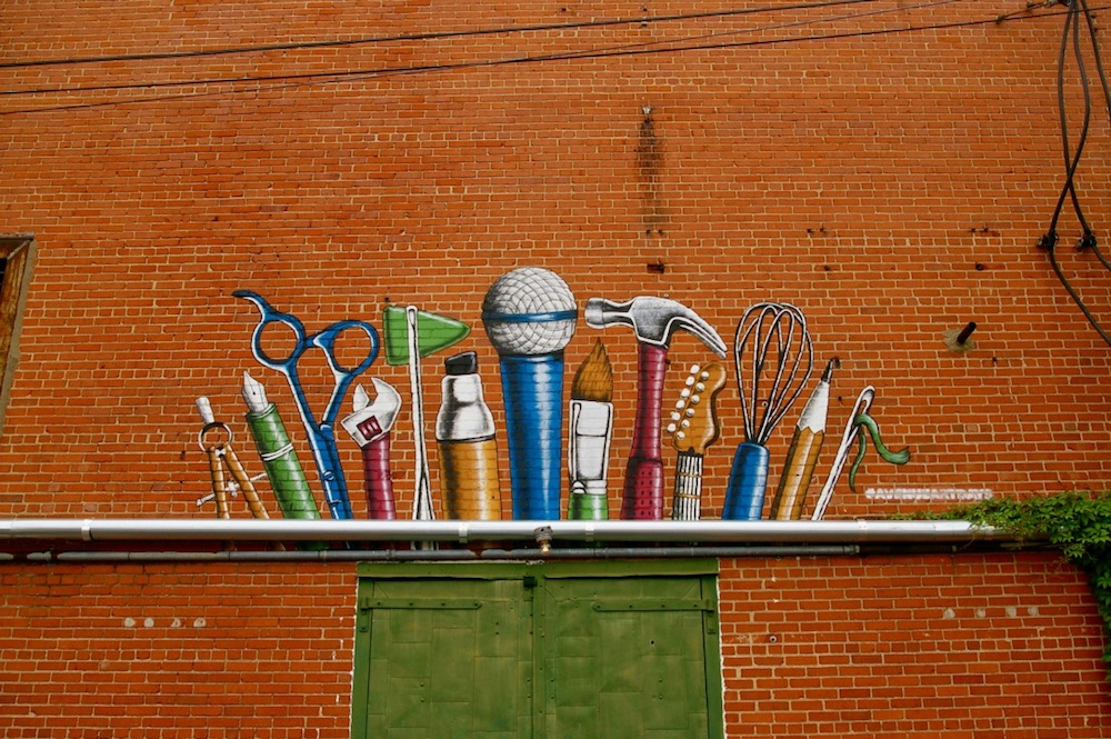 Art supplies painted on a brick wall above green doors in the Douglas Design District of Wichita, Kansas