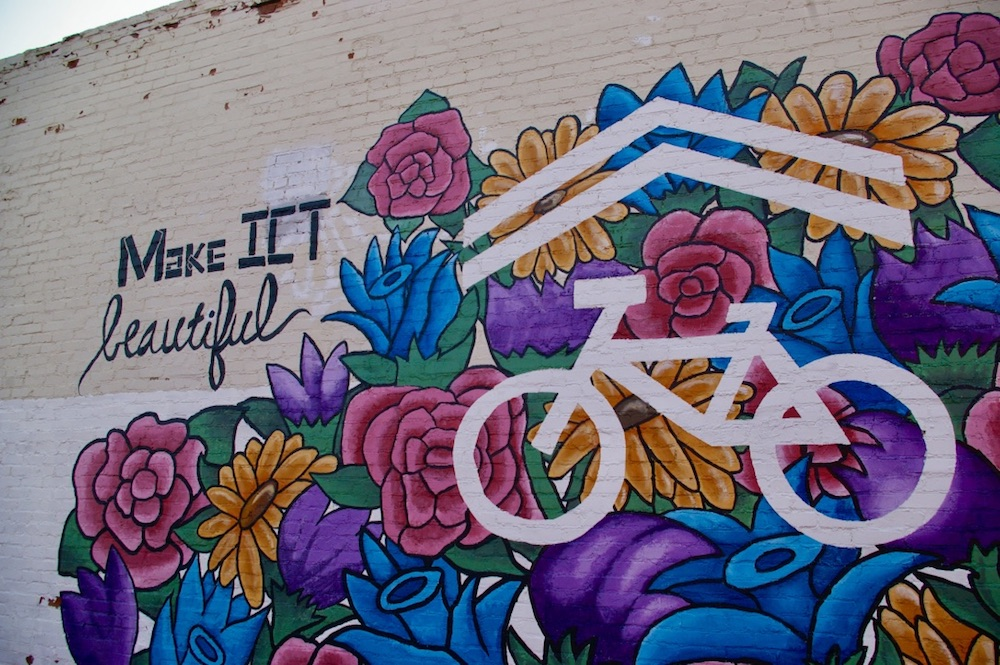 "Colorful floral mural with a bicycle that says ""Make it beautiful"" in the Douglas Design District of Wichita, Kansas"