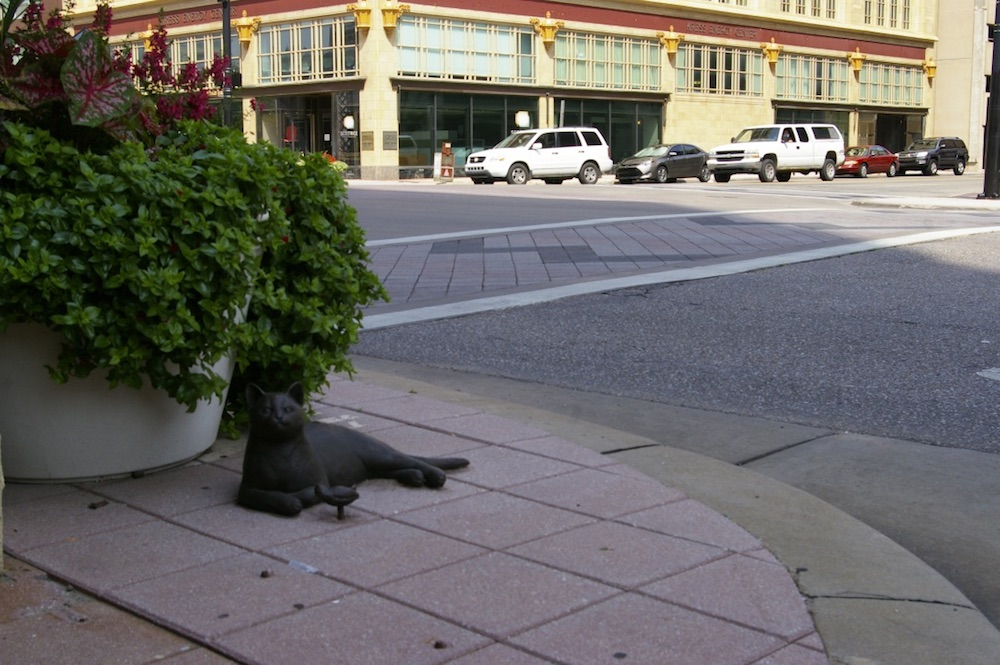 Bronze statue of cat and a bird on a street corner in downtown Wichita, Kansas