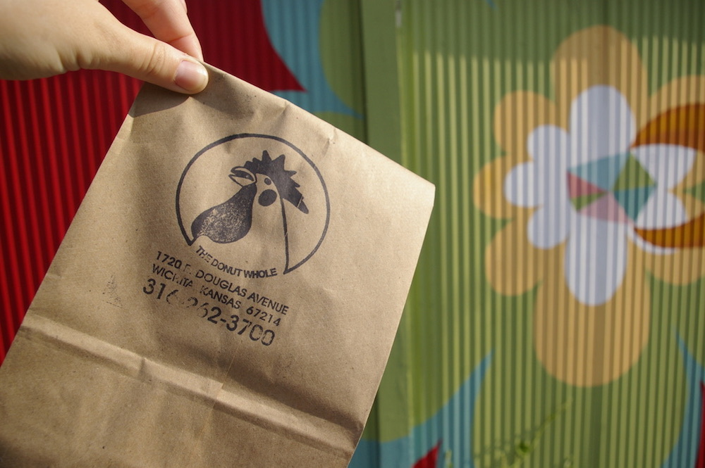 Paper bag from The Donut Whole in front of mural in Wichita, Kansas