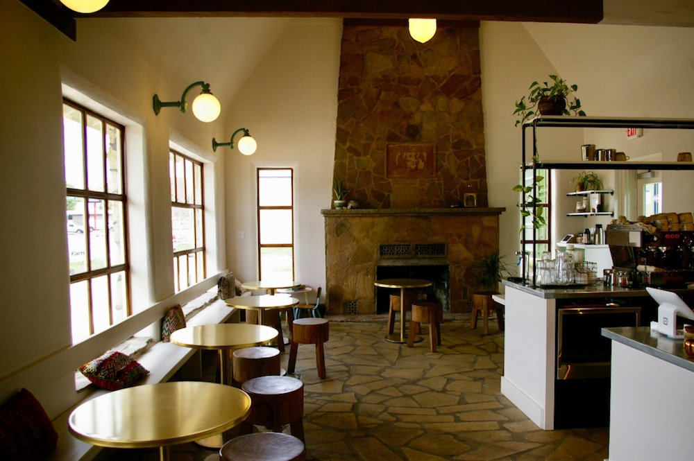 Interior of Little Lion Ice Cream in Wichita, Kansas with stone fireplace and gold circular tables