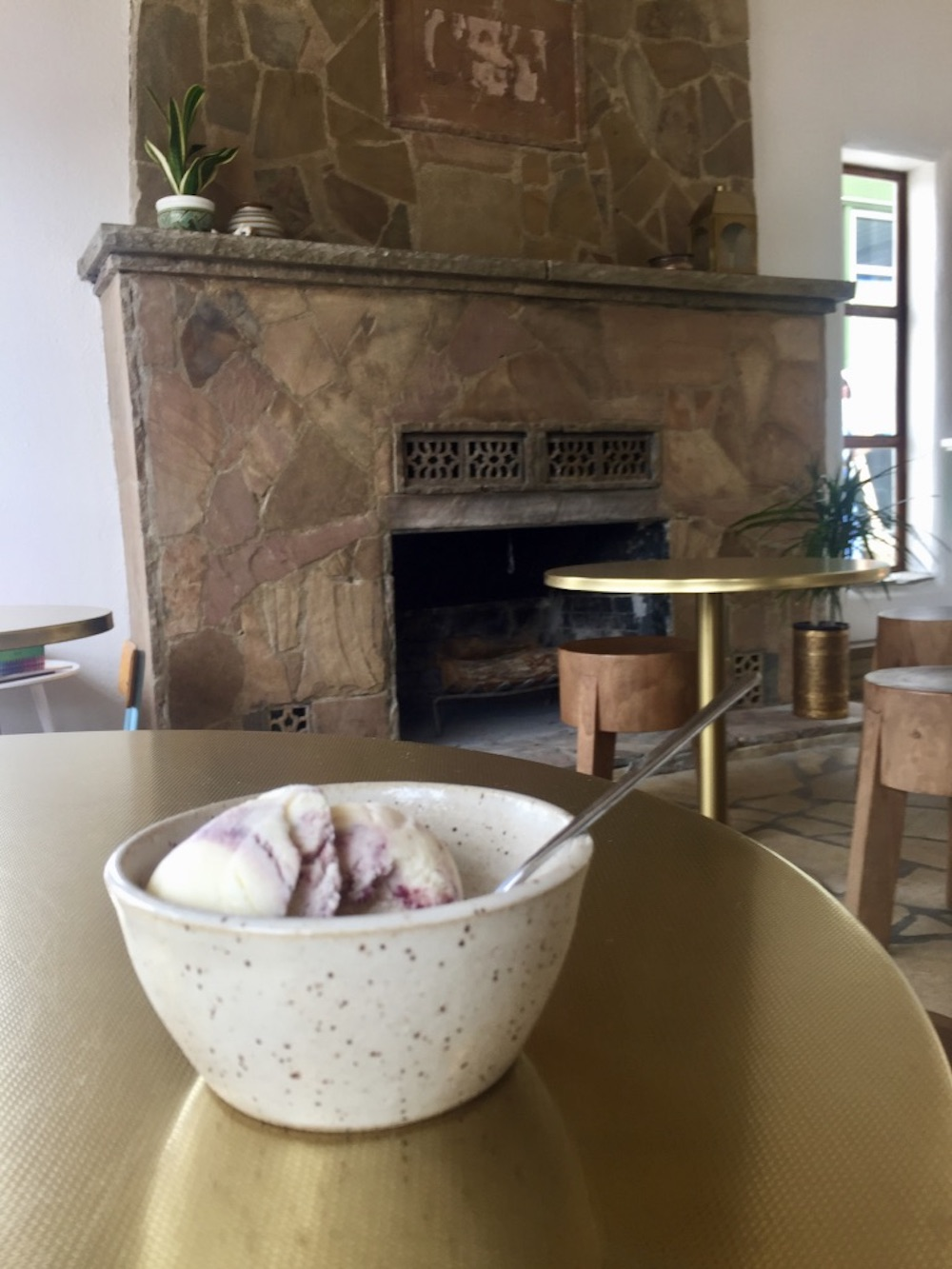 Speckled ceramic bowl of blackberry ice cream on a gold table at Little Lion Ice Cream in Wichita, Kansas