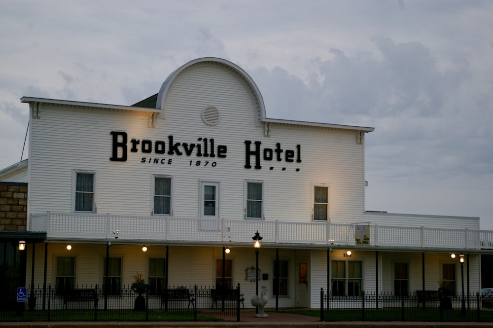 White facade with curved roof and wraparound porch of the Brookville Hotel in Abilene, Kansas