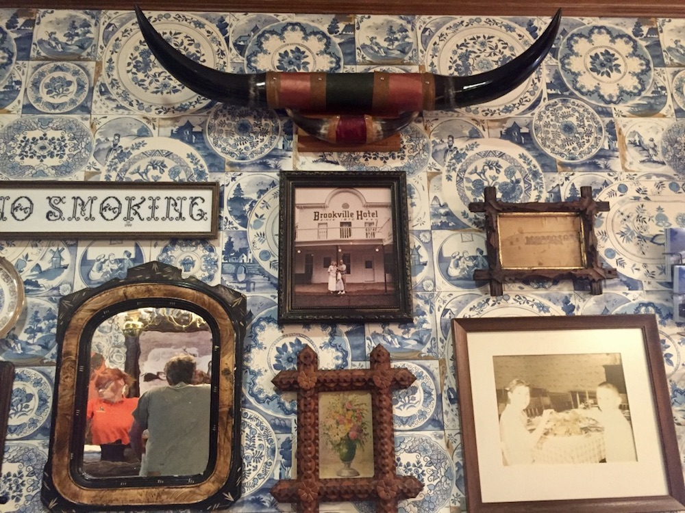 Longhorns and various artifacts mounted on a wall with blue and white floral wallpaper at the Brookville Hotel in Abilene, Kansas
