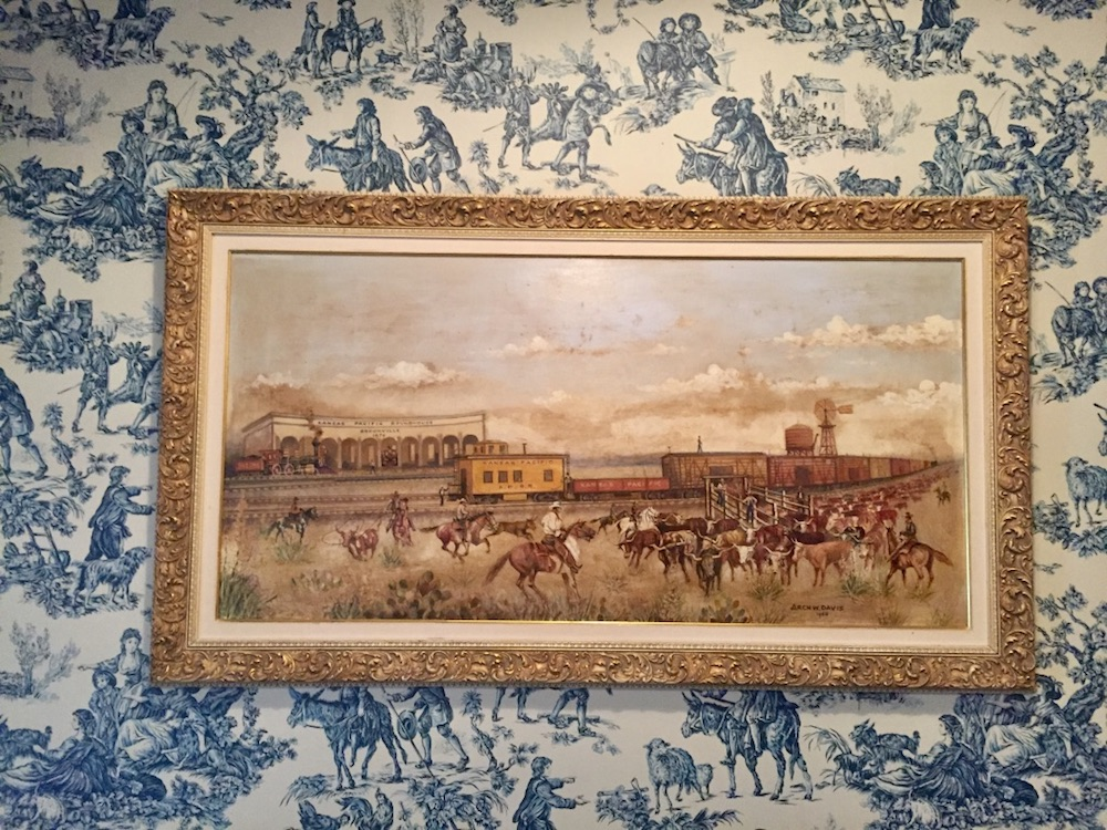 Painting of Kansas cowboys on the Chisholm Trail against blue and white wallpaper at the Brookville Hotel in Abilene, Kansas