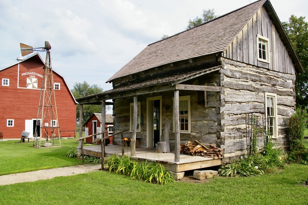 Historic log cabin with red barn in the background on the grounds of the Dickinson County Heritage Center in Abilene, Kansas