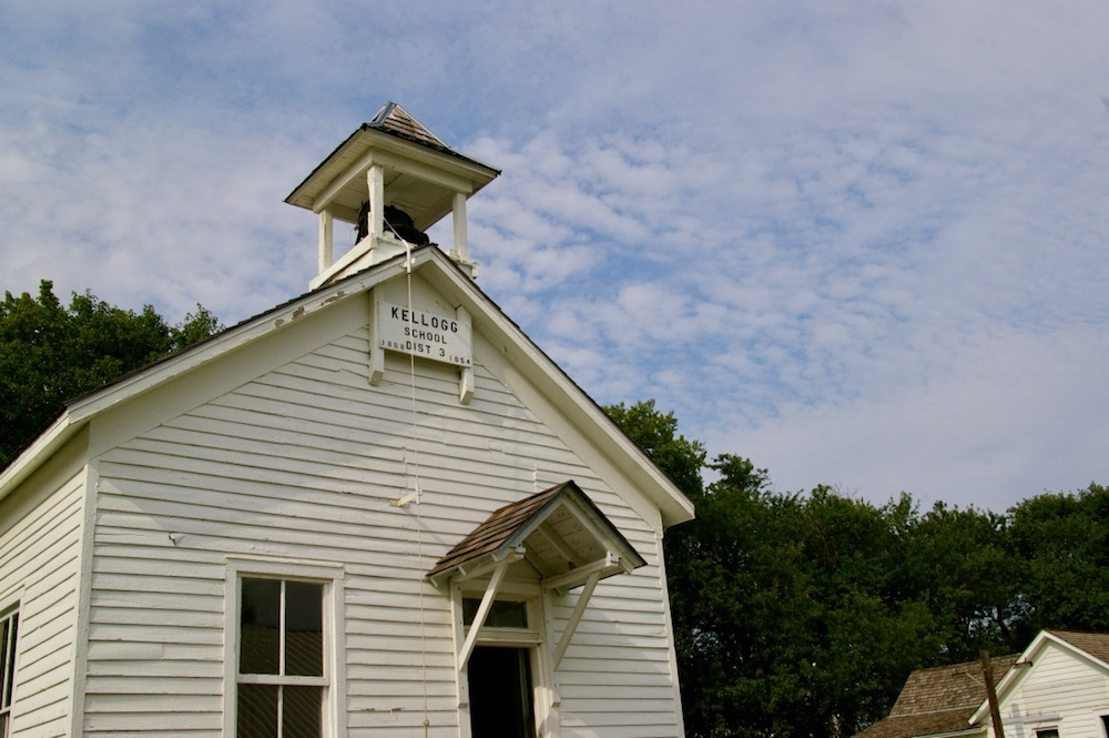White schoolhouse with bell tower on the grounds of the Dickinson County Heritage Center in Abilene, Kansas