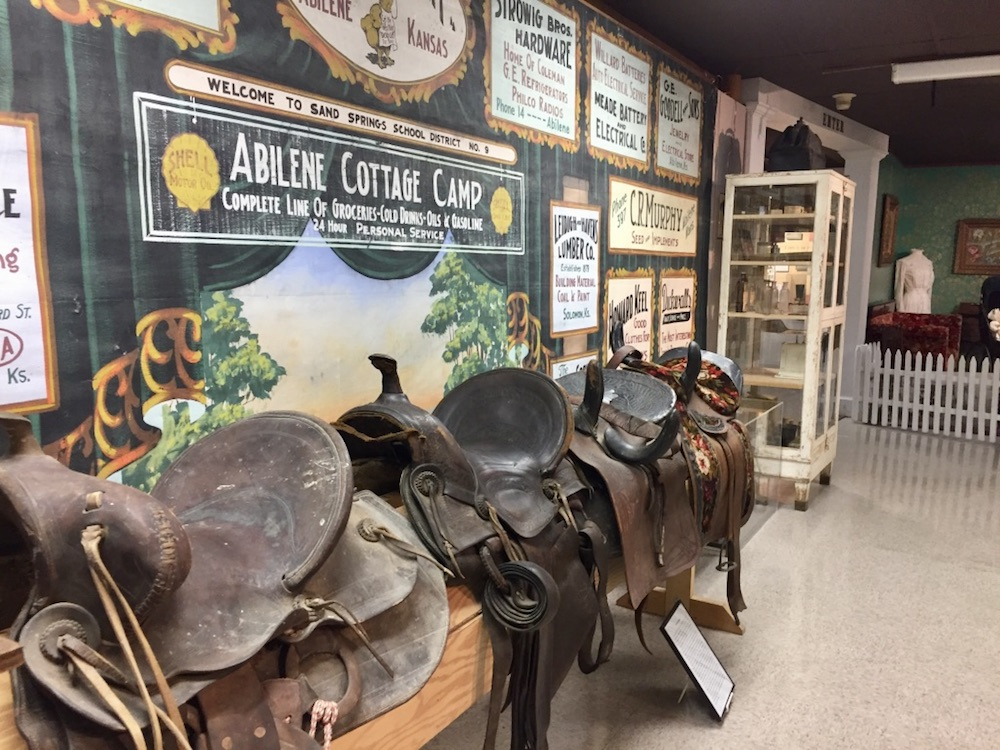 Display of leather saddles in front of information about the Abilene Cottage Camp at the Dickinson County Heritage Center in Abilene, Kansas