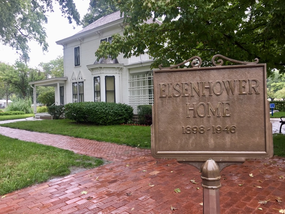 Bronze sign reading Eisenhower Home in front of a white farmhouse at the Eisenhower Presidential Library & Museum in Abilene, Kansas