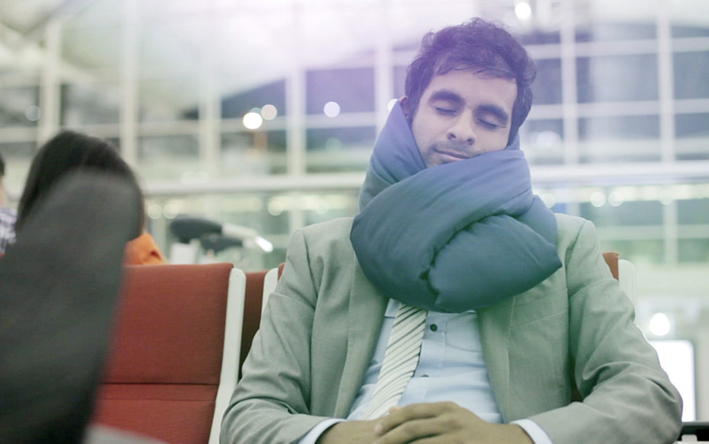 Man wearing Huzi Infinity Pillow in an airport