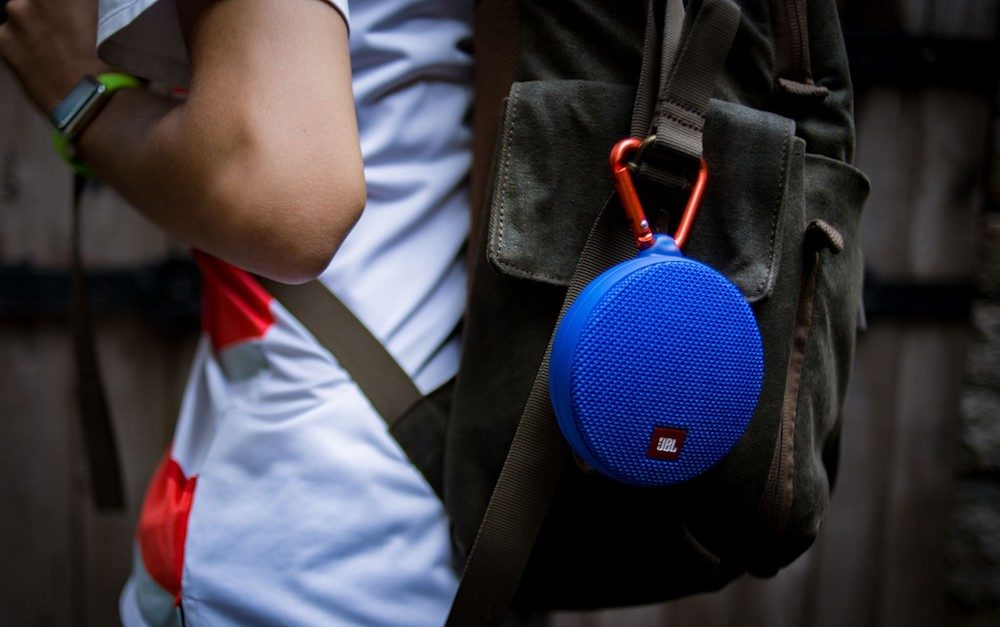 Blue waterproof JBL Clip speaker attached to a backpack