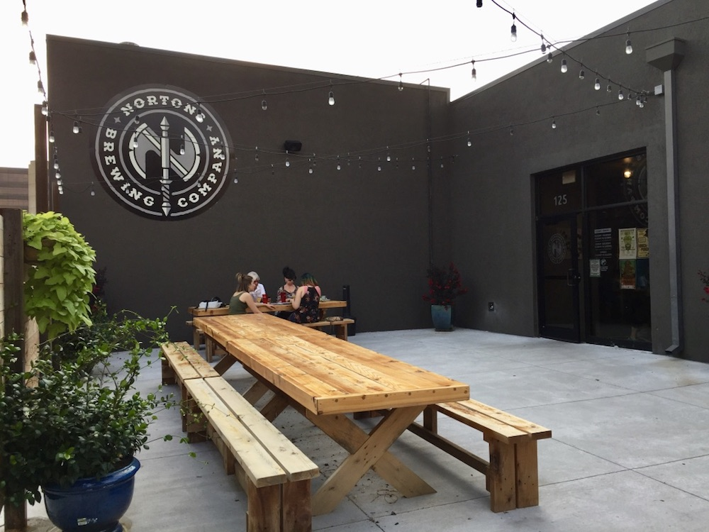 Black exterior of building with long wooden picnic table and strand lighting at Nortons Brewing Company in Wichita, Kansas