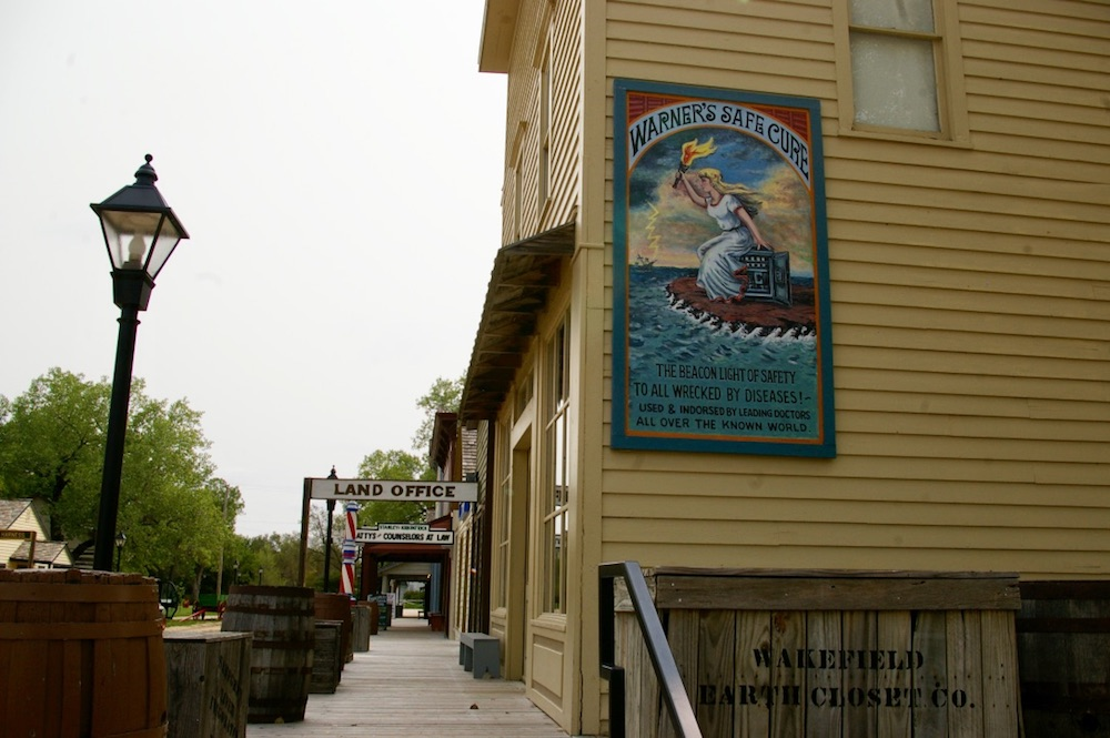 Yellow building with vintage poster and historic boardwalk in the Old Cowtown Museum in Wichita, Kansas
