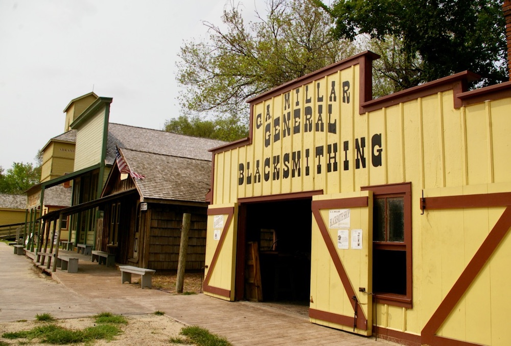 Bright yellow and orange blacksmith shop at the Old Cowtown Museum in Wichita, Kansas