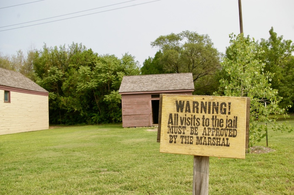 Warning side outside of original jail building at the Old Cowtown Museum in Wichita, Kansas