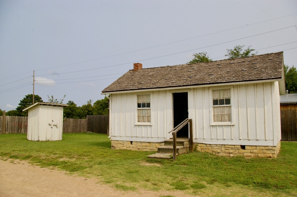Historic homestead with white board exterior at the Old Cowtown Museum in Wichita, Kansas
