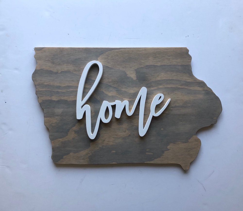 "Wooden sign in the shape of Iowa reading ""home"" by Rosella Margaret"