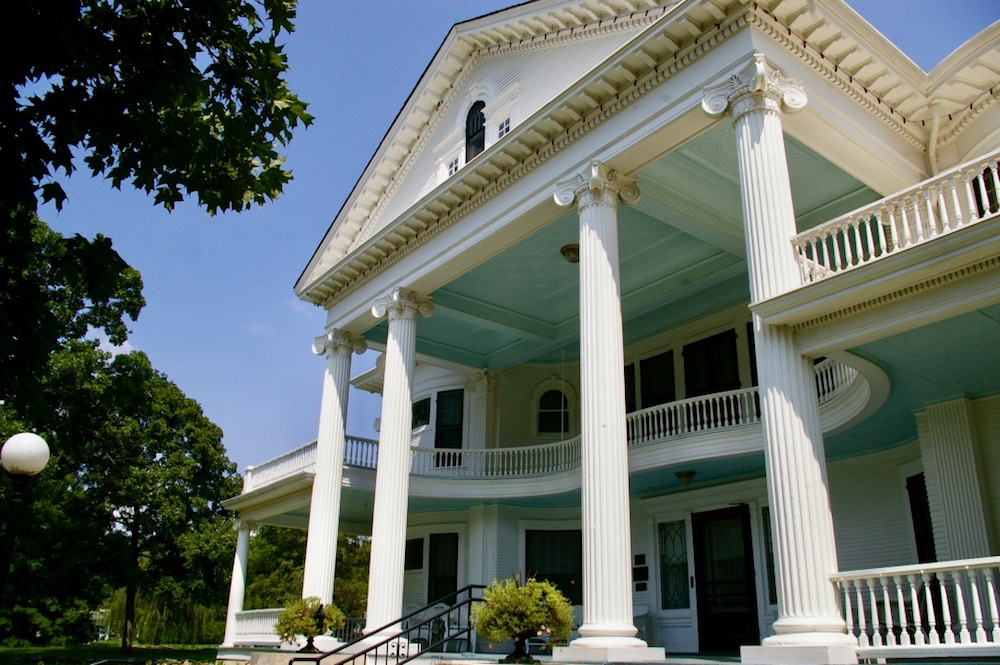Exterior of home with tall white columns and large wraparound porch painted with a baby blue ceiling at the Seelye Mansion in Abilene, Kansas