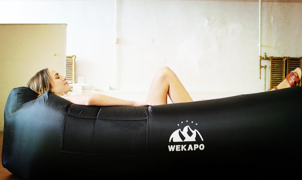 Black WEKAPO inflatable lounger with person relaxing in it
