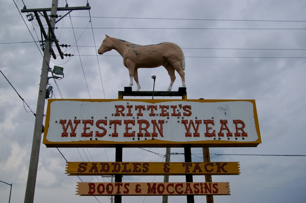 Sign for Rittel's Western Wear with plastic horse on top in Abilene, Kansas
