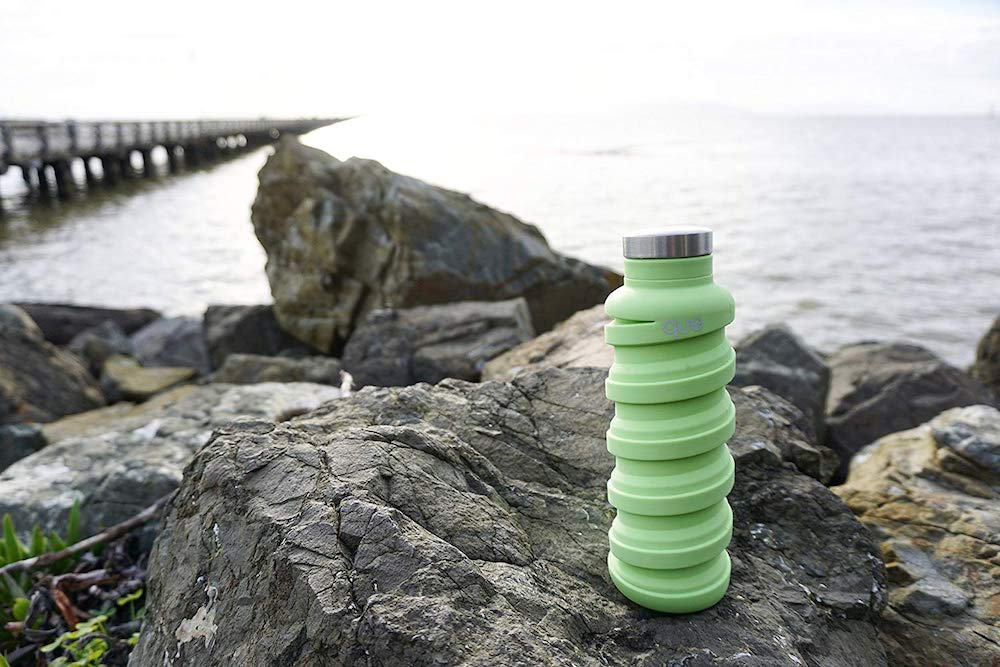 Teal silicone que collapsable water bottle sitting on rocks