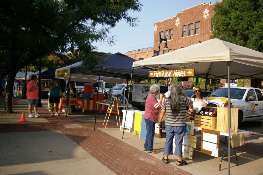 Customers shopping at a booth at the Old Town Farmers' Market in Wichita, Kansas