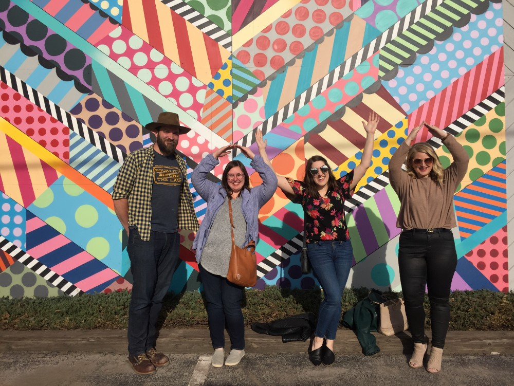 Four people standing in front of a mural spelling Iowa with their arms on a tour with the Iowa Tour Company in Des Moines, Iowa